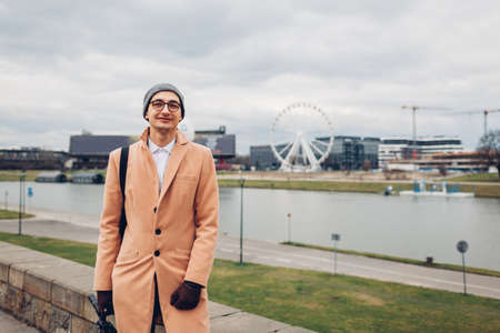Young man tourist walking along pier by Wisla river in Krakow, Poland enjoying Ferris wheel landscape. Europe spring trip. Traveling Фото со стока