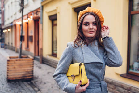 Portrait of stylish young woman wearing yellow knitted beret, grey coat holding purse on street outdoors. Spring fashion female accessories and clothes. Trendy 2021 colors