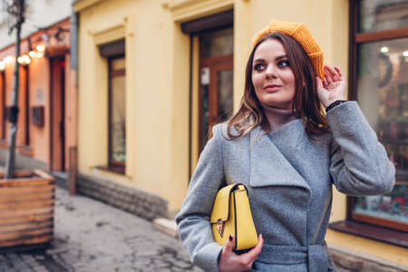 Portrait of stylish young woman wearing yellow knitted beret grey coat holding purse on street outdoors. Spring fashion female accessories and clothes. Trendy 2021 colours