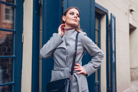 Beauty portrait of stylish young woman posing in city wearing coat with purse by cafe showcase outdoors. Spring fashionable female accessories.