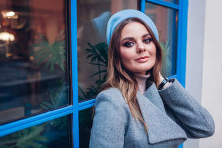 Close up portrait of stylish woman wearing coat blue beret by window outdoors. Spring fashionable female accessories. Trendy retro clothes. Make up