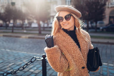 Stylish woman wearing teddy coat beret sunglasses gloves and holding purse outdoors. Spring fashionable female accessories. Trendy clothes 版權商用圖片