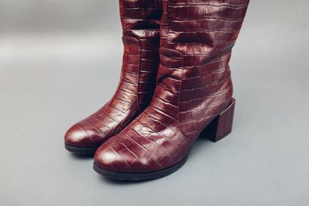 Shoes, stylish burgundy crocodile skin leather boots for women. Female spring fashion. Trendy footwear on grey background.