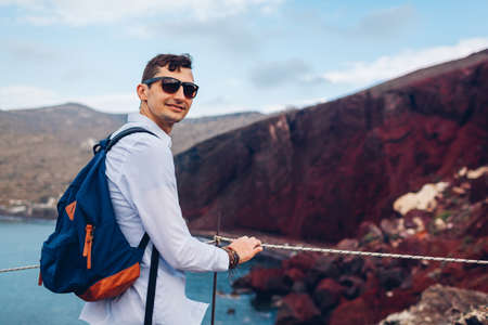 Tourist enjoying Red beach, Aegean sea and mountains landscape from view point in Akrotiri, Santorini island, Greece. Happy man backpacker traveling