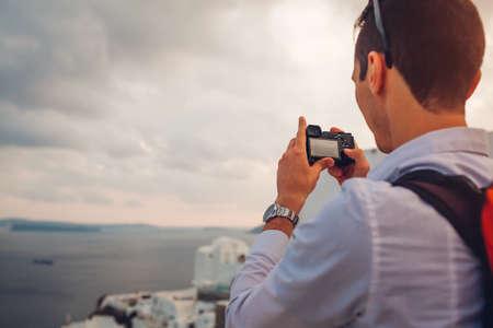 Santorini traveler man taking photo of Caldera from Oia, Greece on camera. Tourism, traveling, summer vacation. Tourist admiring Aegean sea landscape. Фото со стока