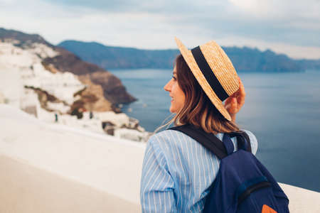 Tourist woman walking on Santorini island, Greece enjoying sea and city landscape. Traveler with backpack admires Caldera view in Oia