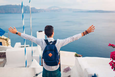 Santorini island traveler man enjoying Caldera view from Oia, Greece with arms raised. Traditional white houses and sea landscape. Tourism, traveling, summer vacation
