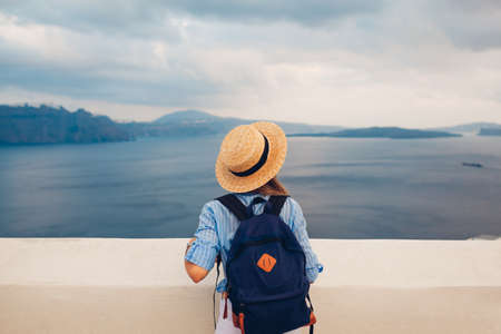 Tourist woman walking on Santorini island, Greece enjoying sea landscape. Traveler with backpack enjoys Caldera view in Oia