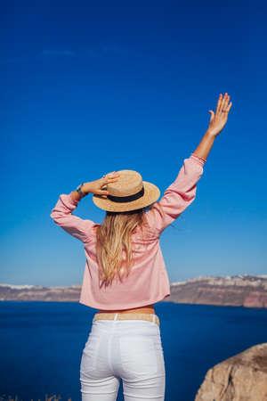 Traveler woman walking on Santorini island, Greece enjoying sea landscape. Happy girl enjoys Caldera view with arm raised. Summer vacation