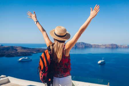 Happy woman traveler walking raising hands in Thera, Santorini island, Greece enjoying sea landscape and cruise ships. Summer vacation Фото со стока