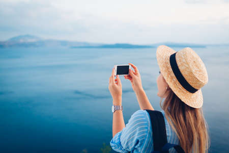 Tourist woman taking pictures on phone of Caldera in Oia on Santorini island, Greece enjoying Aegean sea landscape. Traveler with backpack admires view