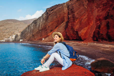 Young traveler woman relaxing sitting on Red beach rock on Santorini island Greece admiring seaside view, mountain landscape. Tourist enjoys summer vacation