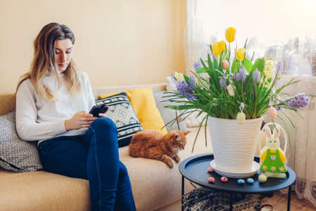 Easter home decor. Woman and cat relax on couch. Spring blooming flowers in pot decorated with eggs and bunny. Yellow hyacinths, tulips, muscari in blossom