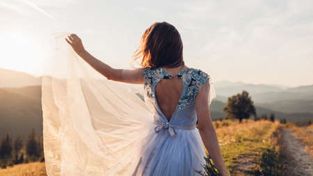 Beautiful bride dancing in blue wedding dress with embroidery and bare back in mountains at sunset. Woman holds flowers. Wedding in Carpathians