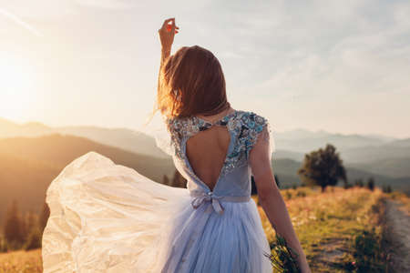 Beautiful bride dancing in blue wedding dress with embroidery decoration and bare back in mountains at sunset. Woman holds flowers. Wedding in Carpathians