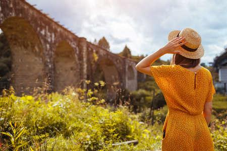 Tourist woman enjoying view of viaduct railway bridge in Vorokhta. Trip to summer Carpathian mountains in Ukraine. Travelling around Europe