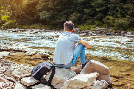 Man tourist relaxing by mountain river enjoying natural landscape. Traveler backpacker sitting on rock. Summer tour to Carpathians