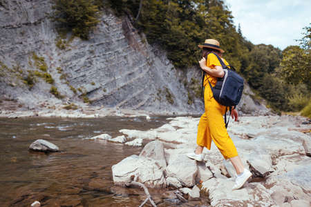 Happy tourist woman hiking by mountain river enjoying landscape. Traveler walking with backpack along rocks. Summer trip close to nature