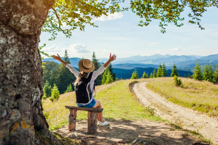 Trip to Carpathian mountains. Woman hiker traveler relaxing admiring landscape with arms raised under tree with backpack sitting on bench. Traveling in summer Ukraine