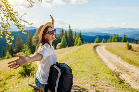 Trip to Carpathian mountains. Happy woman hiker relaxing admiring landscape view with arms raised under tree with backpack. Traveling in summer Ukraine