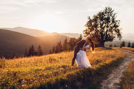 Beautiful newlyweds couple hugging in mountains at sunset. Bride and groom walking in summer Carpathians among flowers. Wedding 版權商用圖片