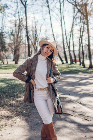 Beautiful woman wearing stylish blazer, hat and boots holding purse in park. Spring female fashionable outfit. 版權商用圖片