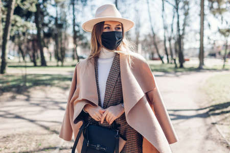 Fashionable woman wears reusable mask outdoors during coronavirus covid-19 pandemic in empty spring park.