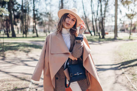 Stylish woman wears hat holding handbag in park. Spring female clothes and accessories. Fashion 版權商用圖片