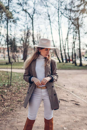 Beautiful woman wearing stylish blazer hat and boots in park. Spring female fashionable outfit in white and brown color. 版權商用圖片