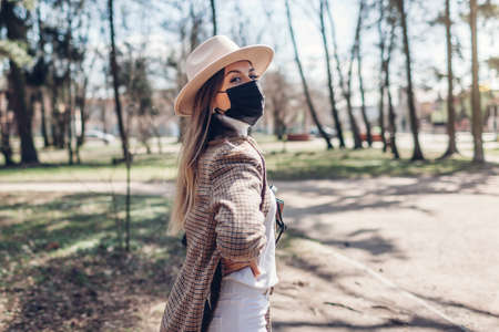 Woman wears reusable mask outdoors during coronavirus covid-19 pandemic in empty spring park. 2021 outfit