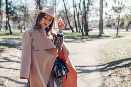 Stylish woman wears hat holding handbag in park. Spring female clothes and accessories in pastel colors. Fashion
