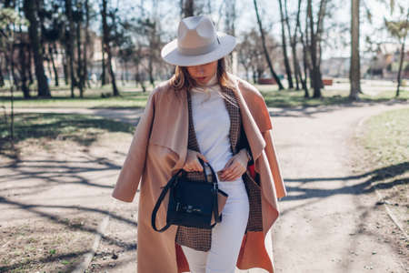 Stylish woman wears hat holding handbag walking in park. Spring female clothes and accessories. Fashion