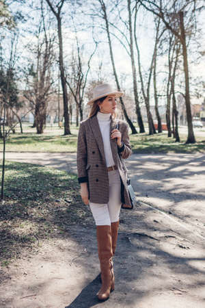 Full body portrait of beautiful woman wearing stylish blazer, hat and boots in spring park. Female fashion 版權商用圖片