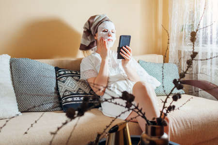 Young woman with facial sheet mask applied looks at smartphone at home after bath relaxing on couch.
