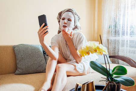Woman with facial sheet mask applied wearing towel on head relaxing at home after bath using smartphone 版權商用圖片