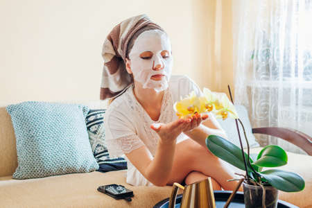 Woman applied facial sheet mask relaxing at home after bath enjoying orchid flowers. Natural cosmetic products