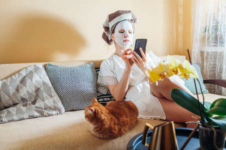 Woman with facial sheet mask applied relaxing at home after bath sitting on couch with cat using phone. Skincare routine 版權商用圖片
