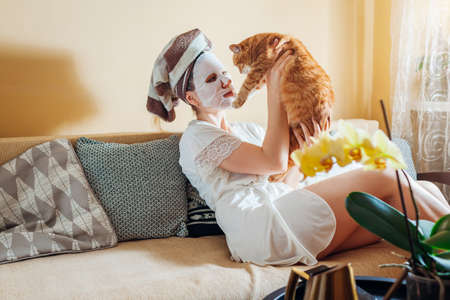 Woman with facial sheet mask applied relaxing at home after bath playing with cat. Enjoying time with pet