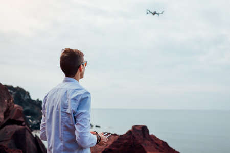 Drone remote control. Videographer operating copter controller by sea. Aerial video shooting of Red beach on Santorini island. Archivio Fotografico