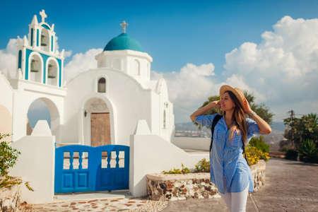 Santorini island traveler exploring greek church architecture in Akrotiri. Woman tourist walking during vacation. Traveling around Europe