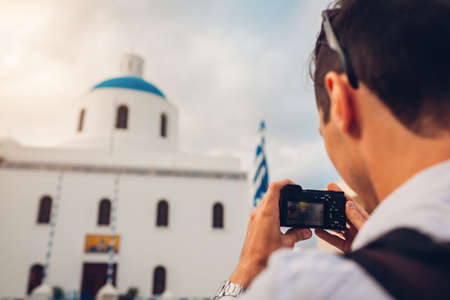 Santorini traveler man taking photo of church with blue dome and flag in Oia, Greece on camera. Tourism, traveling, summer vacation. Traditional architecture