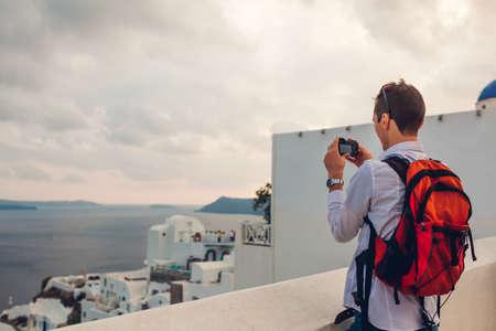 Santorini traveler man taking photo of Caldera from Oia, Greece on camera. Backpacker travels during summer vacation. Tourist admiring Aegean sea landscape.