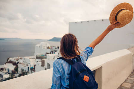 Tourist woman walking on Santorini island, Greece enjoying sea and city architecture landscape. Traveler with backpack admires Caldera view in Oia