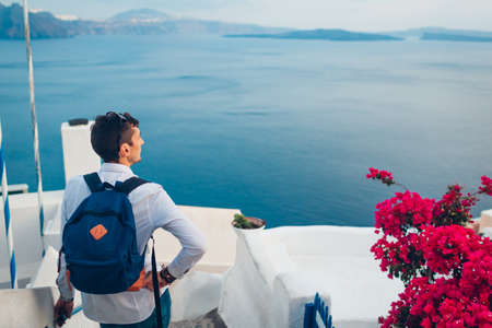 Santorini island traveler man enjoying Caldera view from Oia, Greece. Traditional white houses with bougainvillea flowers and sea landscape. Tourism, traveling, summer vacation Archivio Fotografico