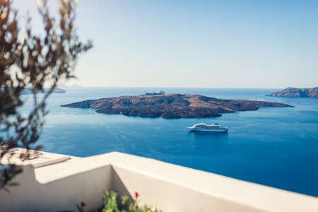 Landscape of Aegean sea with big passenger cruise ship near volcano on island of Santorini, Greece. Caldera view. Tholos Naftilos