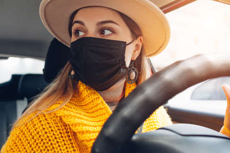 Stylish woman driving car wearing protective mask during coronavirus covid-19 pandemic. Safety measures. Spring fashion
