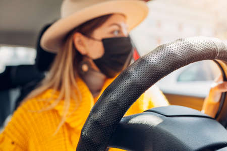 Stylish woman driving car wearing protective mask during coronavirus covid-19 pandemic. Safety measures. Close up of steering wheel