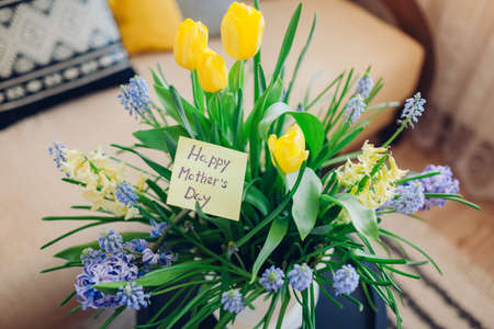 Mother's day present. Pot with blooming spring yellow and blue flowers and greeting card waits for mom at home. Gift for holiday with 2021 colors Archivio Fotografico