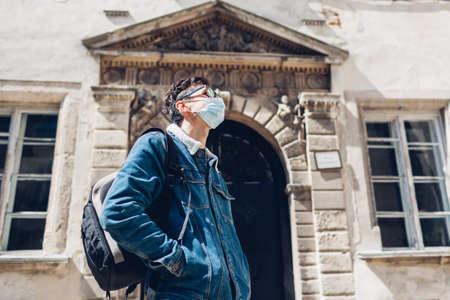 Tourist man walking in Olesko Castle yard wearing mask. Travelling during coronavirus covid-19 pandemic in Ukraine.