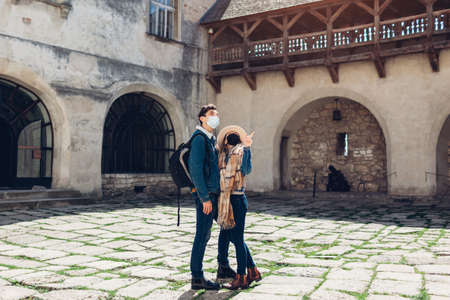 Couple of tourists walking in Olesko Castle yard wearing masks admiring ancient architecture. Travelling during coronavirus covid-19 pandemic in Ukraine.
